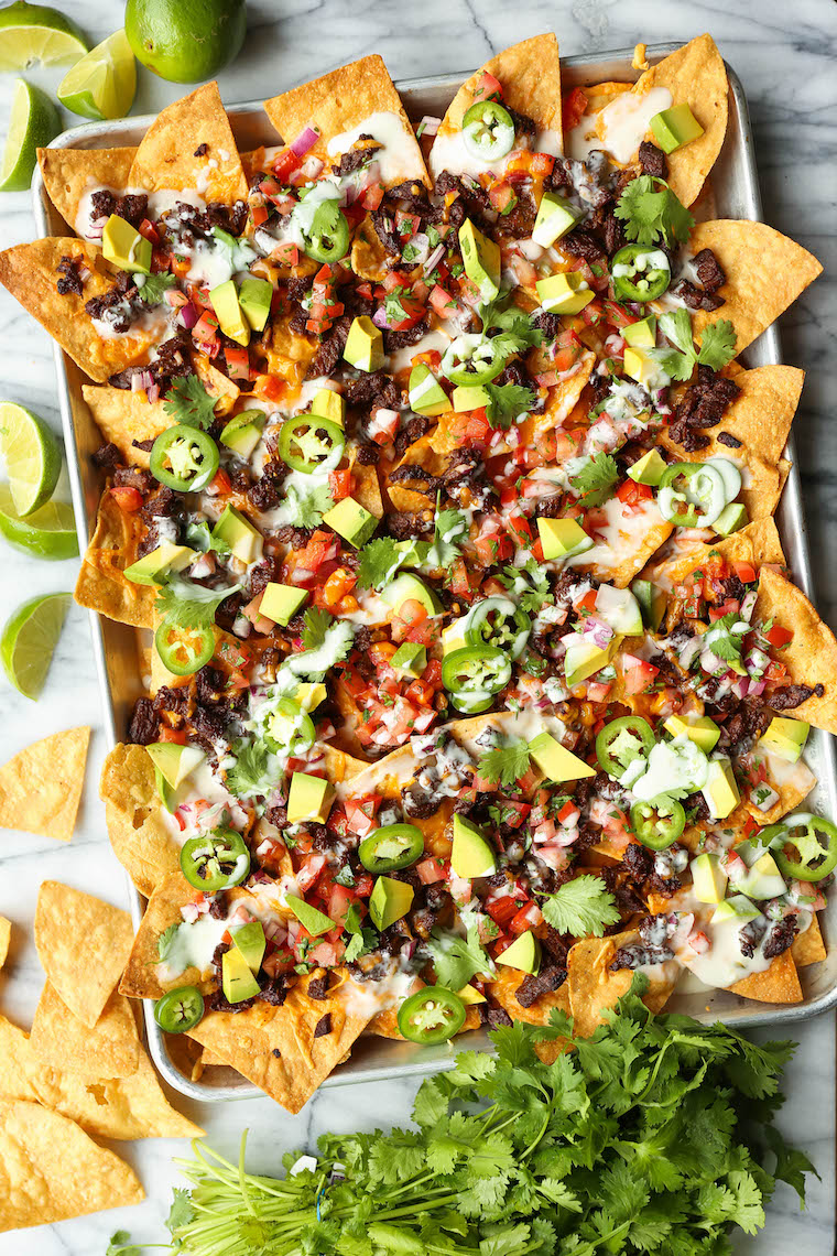 Carne Asada Nachos - BEST NACHOS EVER! Loaded with the easiest, most tender carne asada, sharp cheddar, pico de gallo, avocado, jalapeno + drizzle of queso!
